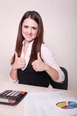 Young Businesswoman Working In Office And Showing Thumb Up Sign