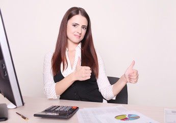 Pretty businesswoman showing thumb up to camera at her desk in h