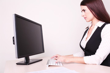 Cheerful businesswoman working at her desk looking at camera in