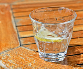 Glass with sparkling water, ice cubes and lemon