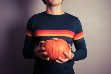 Young man with pumpkin