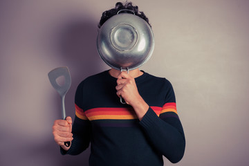 Young man hiding behind colander