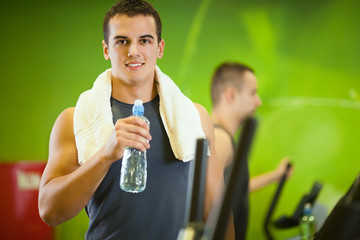 Young man having a break from exercising in the gym