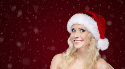 Attractive woman in Christmas cap on purple snowy background