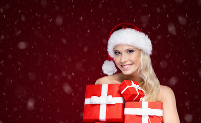 Beautiful lady in Christmas cap holds a set of gifts