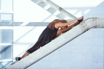 Beautiful ballerina performing right split on a staircase