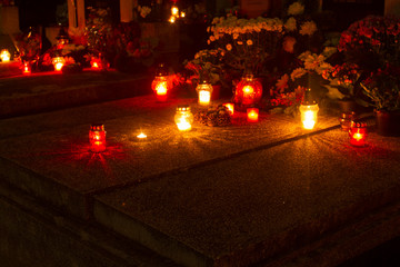 cemetery decorated with candles for All Saints Day at night