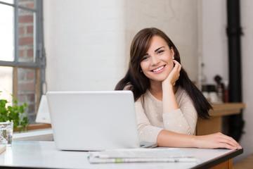 junge frau sitzt am küchentisch mit laptop