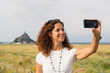 Smiling middle aged woman taking a selfie with mobile phone outd