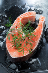 raw salmon steak with dill on ice, top view