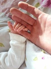Niemowlak trzyma palec taty