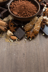 spices for hot chocolate on a wooden background, vertical