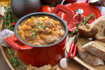 vegetable stew with sausages in a red pan