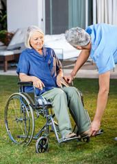 Nurse Adjusting Footrest For Senior Woman On Wheelchair
