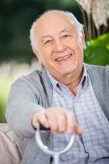 Portrait Of Smiling Senior Man Holding Walking Stick