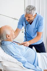 Smiling Caretaker Checking Senior Man's Chest