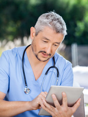 Male Caretaker Using Tablet PC