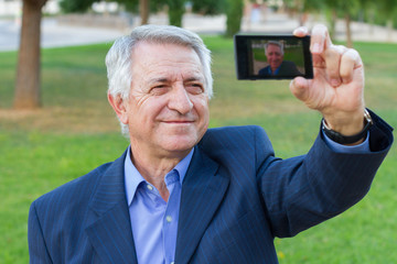 Businessman in a suit taking selfie with limited dof