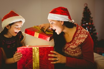 Festive mother and daughter opening a glowing christmas gift