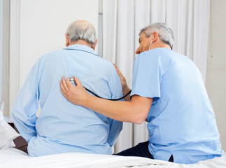 Caretaker Examining Senior Man's Back