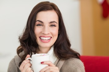 Smiling brunette enjoying a hot chocolate with marshmallow