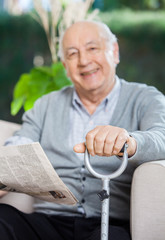 Happy Senior Man With Newspaper And Cane Sitting On Couch