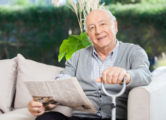Senior Man With Newspaper And Stick Sitting On Couch