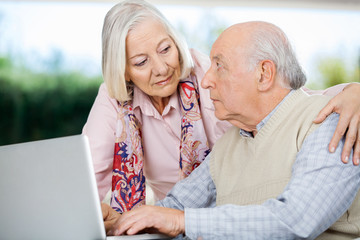 Senior Couple Looking At Each Other While Using Laptop
