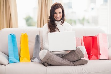 Brunette shopping online with laptop on the couch