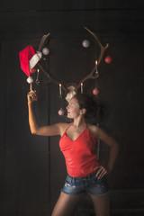 Junge Frau vor weihnachtlich geschmücktem Hirschgeweih
