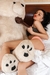 sexy woman lying bed with big teddy bear