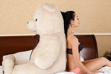 beautiful woman sitting back to back with a big teddy bear