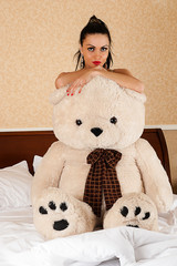 beautiful woman with big teddy bear sitting on the bed