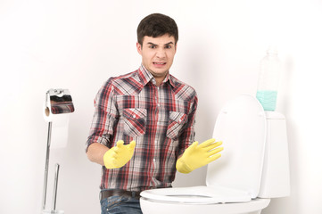 man cleaning toilet with spray cleaner