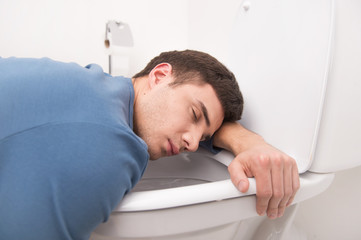 young man lying on toilet seat