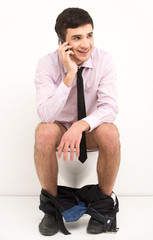 Man with mobile phone sitting on toilet.