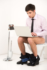 Man with laptop computer sitting on toilet.