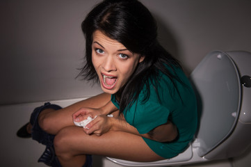 Portrait of young woman shouting in toilet to camera.