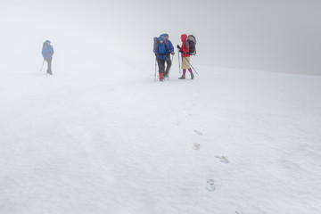 Group of hiker are walking in mist in winter time