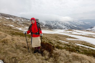 Hiker in winter mountains on cloudy day