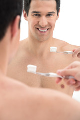 Close up of sexy fit man brushing his teeth.