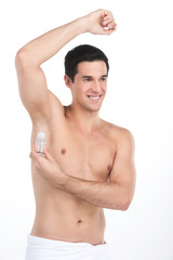 Young handsome men applying deodorant on armpits.