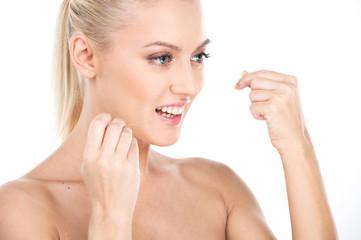 Beautiful young woman using dental floss,