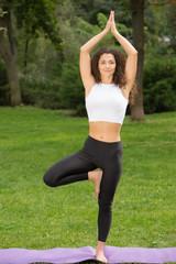 Smiling pretty woman doing yoga exercises
