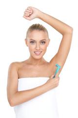Pretty woman shaving armpit with razor.