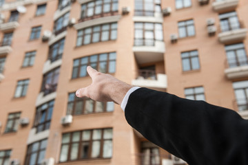 businessman hand pointing in direction of apartment.