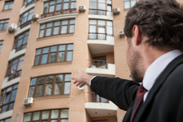 young businessman pointing in direction of apartment.