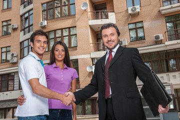 Salesman giving handshake to property owners.