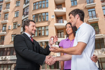 Salesman giving keys to property owners.