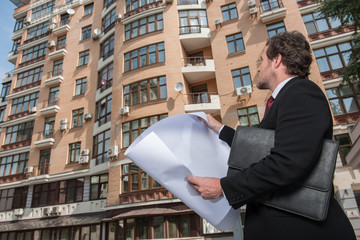Architect looking at plan and apartment building.
